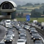"""Motorists drive in traffic on the A7 motorway under a bridge where a security camera is set on August 2, 2014 at the toll station of Vienne, southeastern France, on the first major weekend of the French summer holidays. This weekend is expected to be """"most difficult of the summer"""" for traffic, with hundreds of kilometers of traffic jams, as holiday-makers start or end their holidays. The A7, also known as the """"Autoroute du soleil"""" (the Sun's motorway), links Paris to the French Mediterranean coast.     AFP PHOTO / PHILIPPE DESMAZES        (Photo credit should read PHILIPPE DESMAZES/AFP/Getty Images)"""