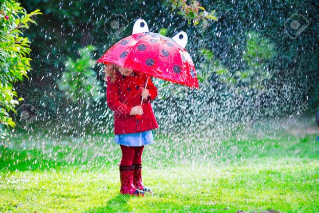 Little girl with red umbrella playing in the rain. Kids play outdoors by rainy weather in fall. Autumn outdoor fun for children. Toddler kid in raincoat and boots walking in the garden. Summer shower.